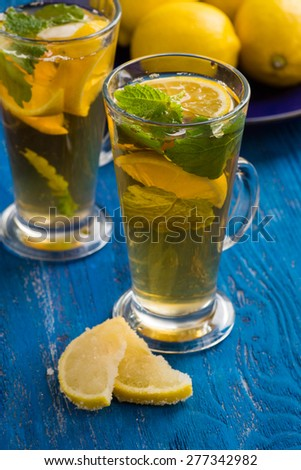 Iced tea with lemon and mint, on the blue wooden table - stock photo