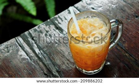 Iced tea with milk on wooden table (Thai beverage) - stock photo