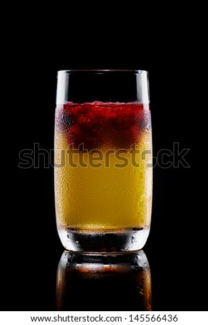 Iced tropical cocktail in a tall glass frosted with moisture with fresh fruit or berries floating at the top on a dark background