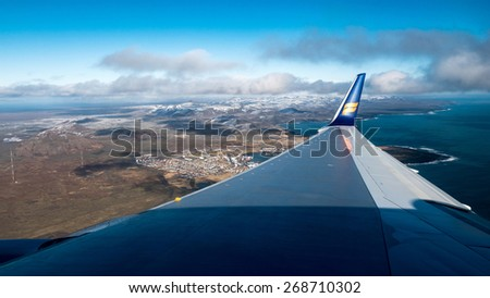 ICELAND - MARCH 23, 2015: An Icelandair jet flies low over Iceland showing the magnificent landscapes below it as it prepares to land at Keflavik International Airport in Reykjavik.  - stock photo
