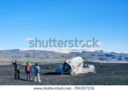 Iceland September 2017 A tourist at Solheimasandur Plane Wreck in a lava desert in South Iceland. Solheimajökull Glacier in the background.