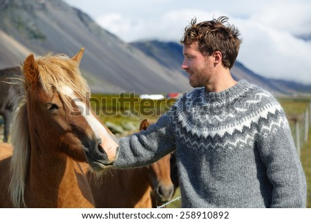 Icelandic horses - man petting horse on Iceland. Man in Icelandic sweater going horseback riding smiling happy with horse in beautiful nature on Iceland. Handsome Scandinavian model. - stock photo