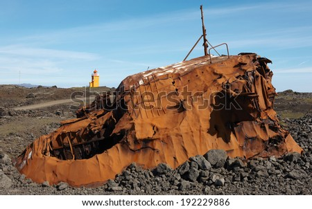 Icelandic landscape with rusted vessel and a lighthouse. Shipwreck - stock photo