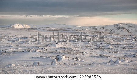 Icelandic snow field full of rocks with stormy sky above - stock photo