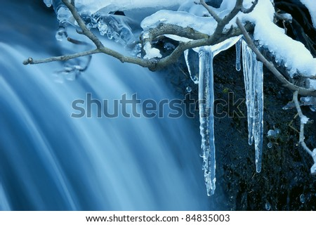Icicle frozen on a branch of a tree near a mountain stream. The winter nature - stock photo