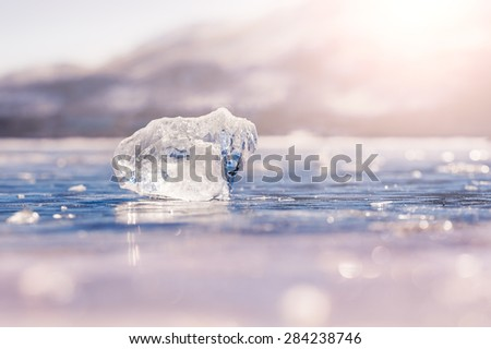 Icicle on the frozen lake. Macro image with small depth of field, bokeh effect.  - stock photo