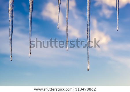 Icicles against a blue sky with clouds. - stock photo