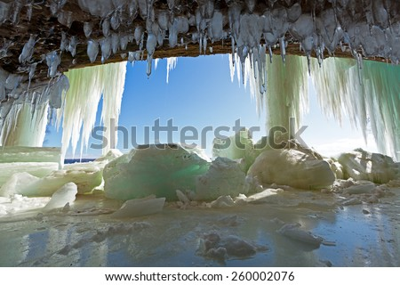 Icicles drape from the ceiling like stalactites in a sea cavern in the Upper Peninsula of Michigan. Ice curtains drape the entrance to this winter wonderland at Grand Island near Munising Michigan. - stock photo