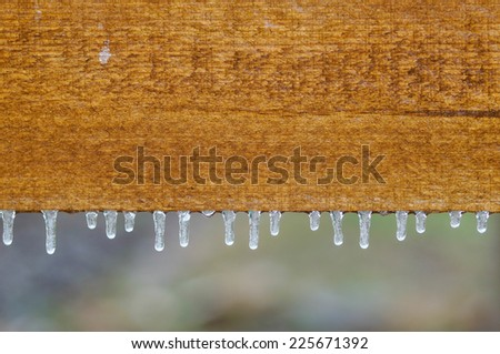icicles hanging down from a wooden fence - stock photo
