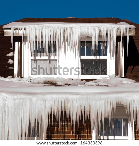 Icicles hanging from a house roof - stock photo