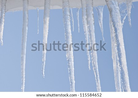 icicles hanging from the roof,against blue sky - stock photo