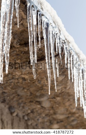 icicles on a roof of a house in winter - stock photo