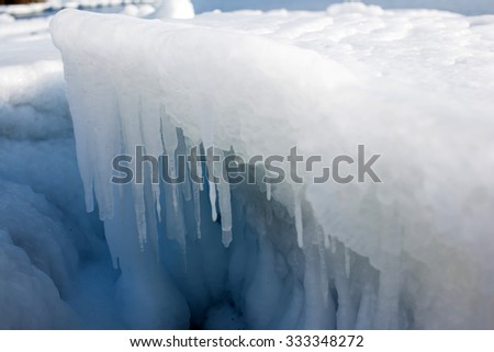 Icicles on the ice, the sea a block of ice on the sea, the ice in the icicles, winter in seas and oceans, Arctic aquatic nature, the ice floe in the ocean, the melting of ice. - stock photo