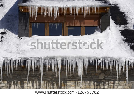 Icicles on the roof of a house in the Pyrenees, Canfranc Valley, Huesca, Aragon, Spain. - stock photo