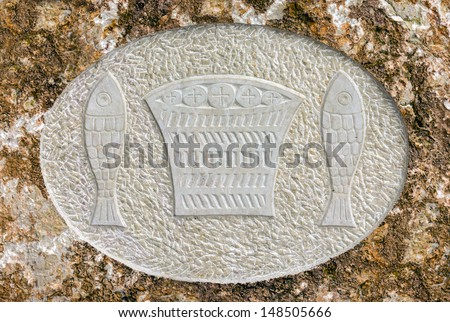 Icon of fishes in rocky Serbian Orthodox Christian monastery Ostrog in mountains, Montenegro. Christian symbols. - stock photo