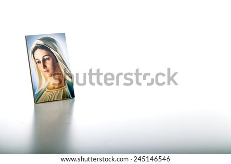 Icon of Our Lady of Medjugorje the Blessed Virgin Mary isolated on white background with matte reflection on white table. - stock photo