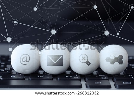 icon on wooden ball of website and internet contact us page concept on computer laptop keyboard and social media diagram - stock photo