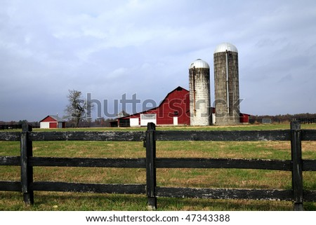 Iconic Barn  and Silo with weathered fence - stock photo