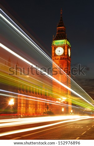Iconic Big Ben Clock Tower viewed from the Westminster Bridge in the evening night with traffic colorful lights trails - stock photo