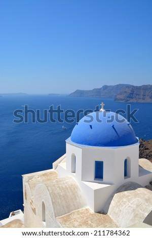 Iconic church with blue cupola and pink bell tower in Oia, Santorini, Cyclades, Greece  - stock photo