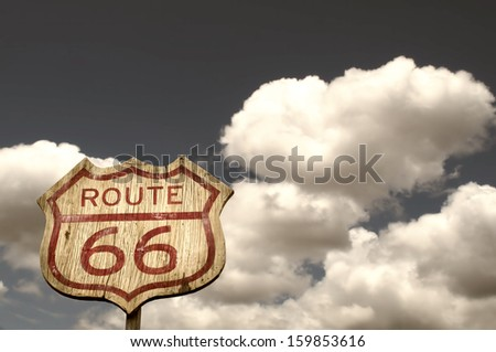 Iconic Route 66 sign framed by the blue cloudy sky - stock photo