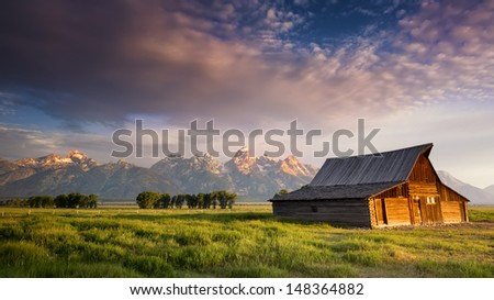 Iconic T. A. Moulton barn and Teton peaks at dawn in Grand Teton National Park, WY - stock photo