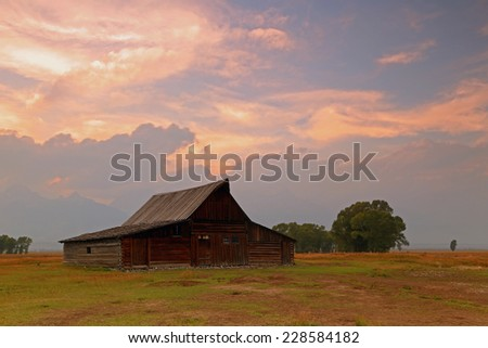 Iconic wooden barn with sunset sky, Wyoming, USA. - stock photo