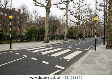 Iconic Zebra crossing with two Belisha Beacons on a quiet tree lined avenue in London.  - stock photo