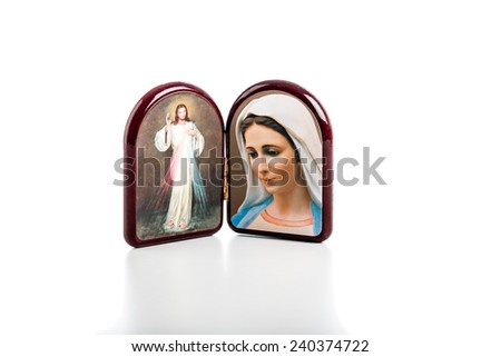 Icons in a wooden rounded case of Merciful Jesus and Our Lady of Medjugorje, the Blessed Virgin Mary isolated on white background with matte reflection on white table. - stock photo