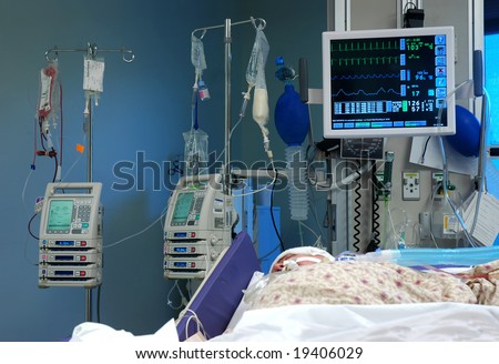 ICU room in a hospital with medical equipments and a patient - stock photo