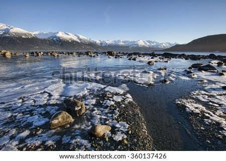 Icy beach near Haines Alaska with ice chunks and snow on an outgoing tide with bright blue sky.