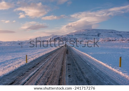 Icy road in the evening with pink and blue sky in Iceland winter with soft and beautiful sun light - stock photo