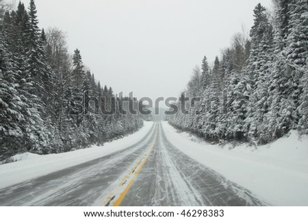 Icy road with fir full of snow all along the road - stock photo