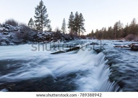 Icy water flows along the Deschutes River at Dillon Falls during sunrise in Central Oregon.