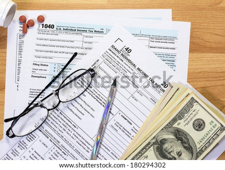 Idaho and federal tax forms with money and medicine