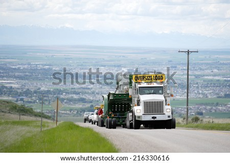 Idaho Falls, ID, June 11, 2010 Over sized cargo being transported to a construction site.  Specialized high horsepower trucks, with many wheeled trailers are used for the transport. - stock photo