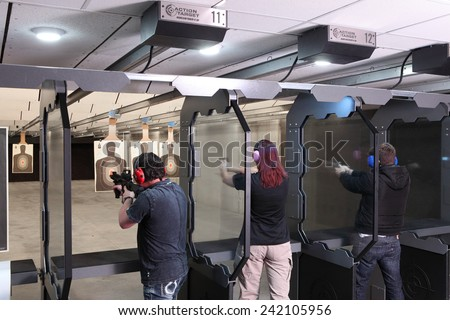 Idaho Falls, Idaho, USA Nov. 18, 2014,  Shooters practicing tactical shooting in a modern indoor gun range. - stock photo