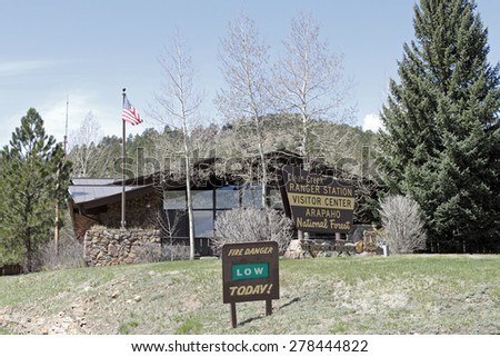 Idaho Springs, CO, USA - April 23, 2014: Clear Creek County Ranger Station and Visitor Center of the Arapahoe National Forest. Front view of a forest service building with trees, lawn and signs  - stock photo