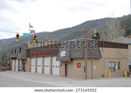 Idaho Springs, CO, USA - April 19, 2014: Front and side of modern fire department building with Colorado and American flags. Semi profile view of an Idaho Springs fire department - stock photo