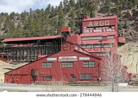 Idaho Springs, CO, USA - April 21, 2014: Large, red painted Argo gold mine and mill with a historical mining museum in front of a rising mountain. The Argo gold mine, mill and museum is a popular spot - stock photo