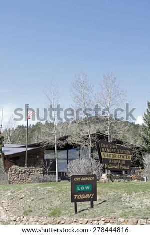 Idaho Springs, CO, USA - April 23, 2014: The Visitor Center and Clear Creek Ranger Station of the  Arapahoe National Forest. Vertical front view of a forest service building with trees, lawn and signs - stock photo