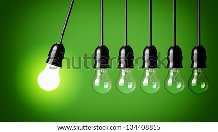 Idea concept on green background. Perpetual motion with light bulbs