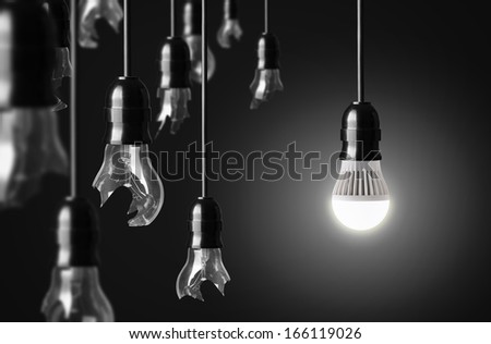 idea concept with broken bulbs and one LED glowing bulb - stock photo