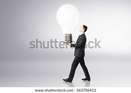 Idea concept with businessman carries big light bulb - stock photo