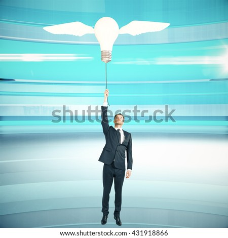 Idea concept with businessman holding lightbulb airballoon with wings on abstract blue background - stock photo