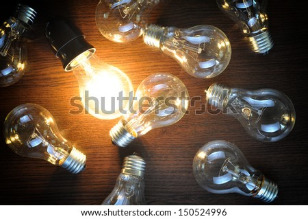 idea concept with glowing bulb on brown wooden background  - stock photo