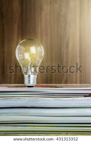 idea concept with light bulbs and magazines. - stock photo