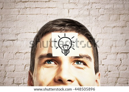 Idea concept with lightbulb sketch drawn on sticker glued to happy guy's forehead on brick background - stock photo