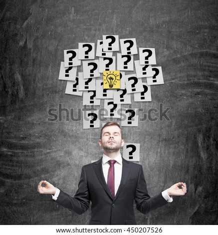 Idea concept with sticker light bulb, question marks and meditating european businessman on chalkboard background - stock photo