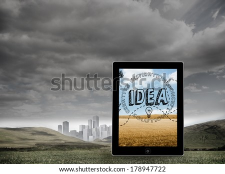 Idea graphic on tablet screen against cityscape in distance under cloudy sky